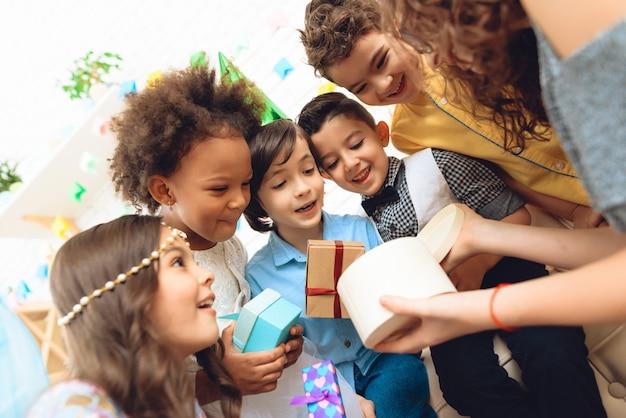 As crianças alegres olham na caixa de presente mantida pela menina do aniversário. Foto Premium