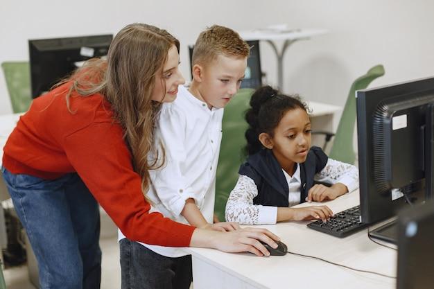 As crianças aprendem a trabalhar no computador. menina africana sentada à mesa. menino e menina na aula de ciência da computação. Foto gratuita