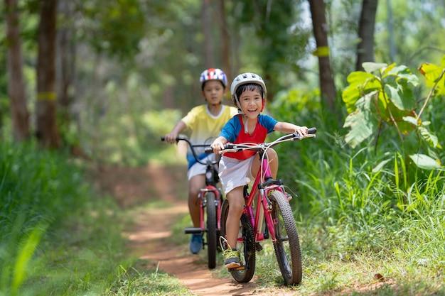 As crianças asiáticas estão felizes com o mountain bike. Foto gratuita