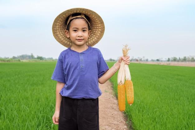 As crianças asiáticas menino usam chapéu de bambu, segurando o milho amarelo na fazenda Foto Premium