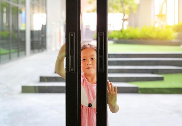 As crianças asiáticas pequenas abrem a porta de vidro na frente da sala de visitas. Foto Premium