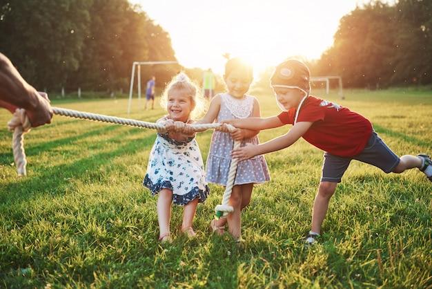 As crianças brincam com o pai no parque. eles puxam a corda e se divertem em um dia ensolarado Foto gratuita