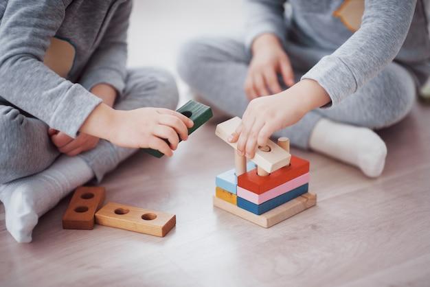 As crianças brincam com um designer de brinquedos no chão do quarto das crianças. duas crianças brincando com blocos coloridos. jogos educativos do jardim de infância Foto gratuita