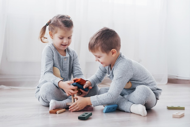 As crianças brincam com um designer de brinquedos no chão do quarto das crianças. duas crianças brincando com blocos coloridos. jogos educativos do jardim de infância Foto Premium