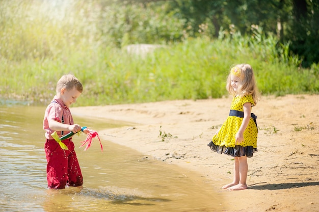 As crianças brincam no rio com barcos Foto Premium