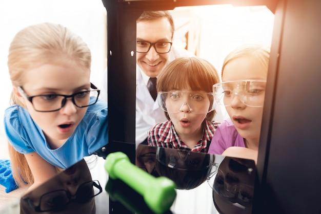 As crianças com o professor olham como a impressora 3d impressa o peso. Foto Premium