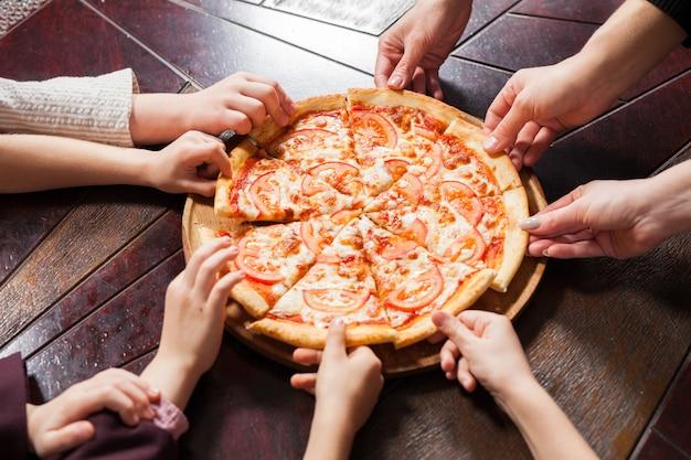 As crianças comem pizza em um restaurante. Foto Premium