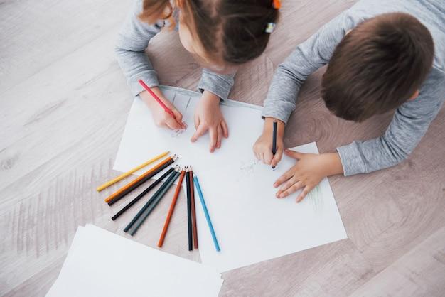 As crianças deitam no chão de pijama e desenham com lápis. pintura bonito da criança por lápis Foto Premium