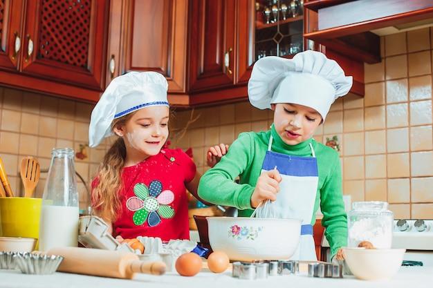 As crianças engraçadas da família feliz estão preparando a massa, assar biscoitos na cozinha Foto gratuita