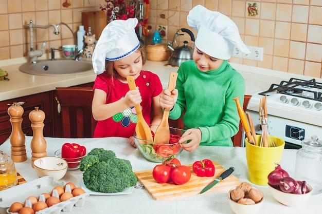 As crianças engraçadas da família feliz estão preparando a uma salada de legumes fresca na cozinha Foto gratuita