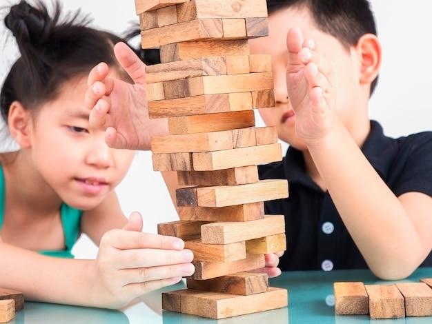 As crianças estão jogando jenga, um jogo de torre de blocos de madeira Foto gratuita