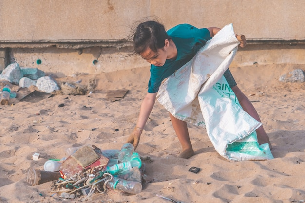 As crianças estão pegando garrafa de plástico e gabbage que encontraram na praia para o conceito de limpeza ambiental Foto Premium