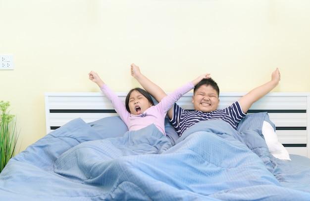 As crianças estão se esticando na cama depois de acordar, Foto Premium
