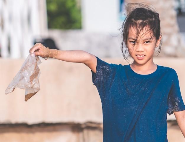 As crianças estão segurando o saco de plástico que ele encontrou na praia Foto Premium