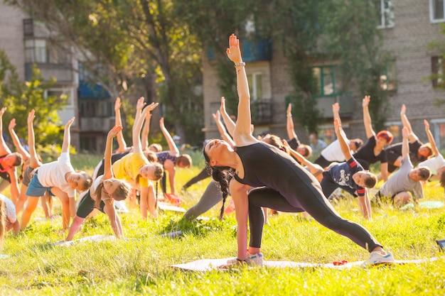 As crianças fazem yoga com um treinador ao ar livre. Foto Premium