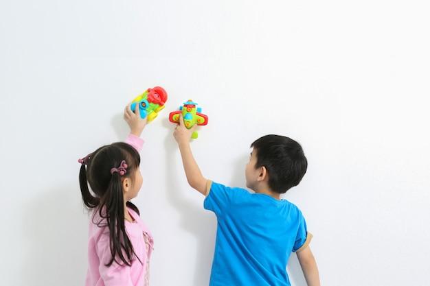 As crianças felizes da idade pré-escolar brincam com o brinquedo plástico colorido. Foto Premium
