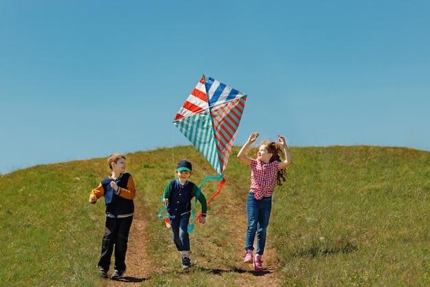 As crianças gostam de brincar com um papagaio voador. Foto Premium