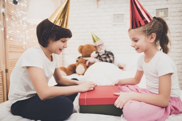 As crianças impertinentes abrem o presente de aniversário que o vovô dorme. Foto Premium