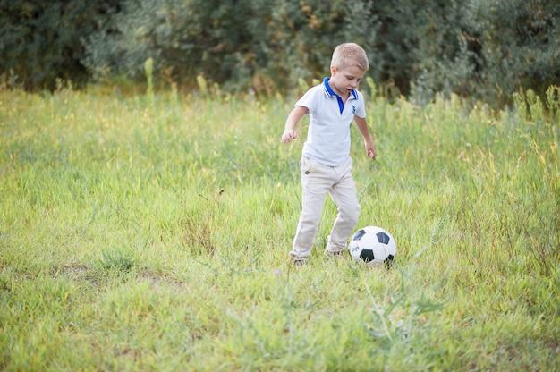 As crianças jogam bola de futebol no campo. vestido com roupas esportivas Foto Premium