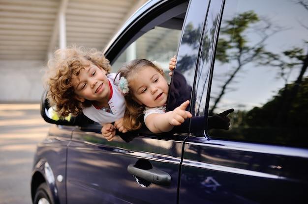 As crianças olham para fora de uma janela de carro Foto Premium