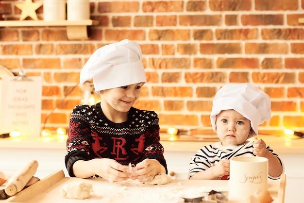 As crianças são cozidas e jogadas com farinha e massa na cozinha Foto Premium