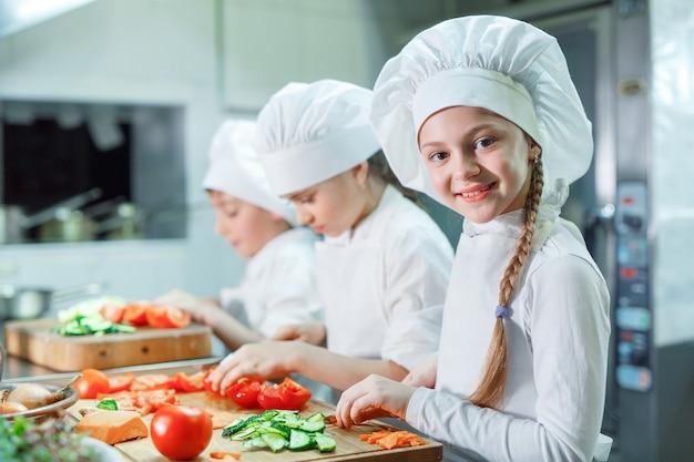 As crianças trituram vegetais na cozinha. Foto Premium
