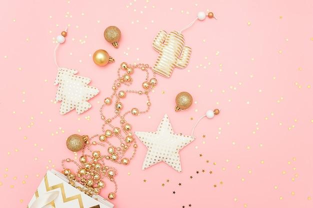 As decorações douradas do natal voam fora das estrelas do saco e dos confetes no rosa feliz natal ou no feliz ano novo conceito. Foto Premium