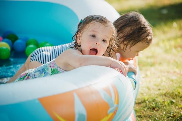 As duas meninas brincando com brinquedos na piscina inflável no dia ensolarado de verão Foto gratuita