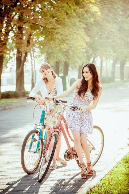 As duas meninas com bicicletas no parque Foto gratuita