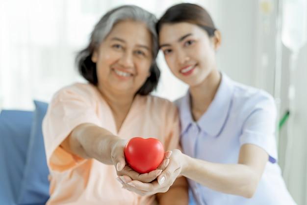 As enfermeiras cuidam bem de pacientes idosos em leitos hospitalares, sentem felicidade - conceito médico e de saúde Foto gratuita