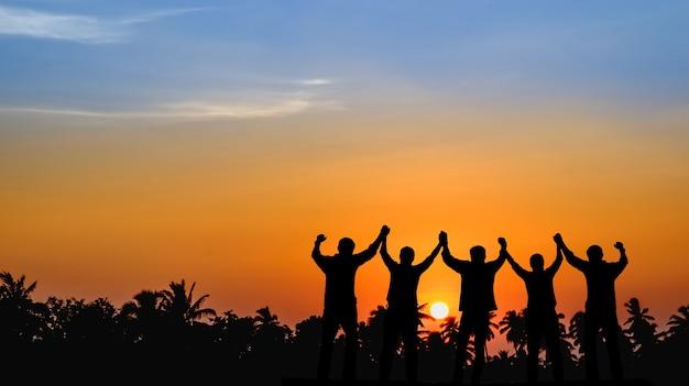 As equipes que estão dispostas a compartilhar o sucesso estão unidas, de mãos dadas, olhando para o pôr do sol. Foto Premium