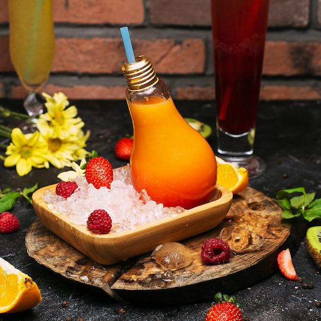 As garrafas de vidro da ampola com suco de frutos tropicais alaranjado fresco na placa com congre cubos e strawbesrries. relaxamento de férias desintoxicação limpeza bem-estar Foto gratuita