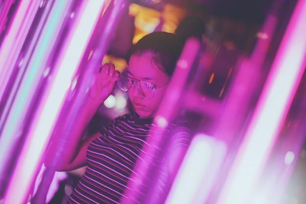 As jovens mulheres asiáticas que vestem vidros estão olhando as luzes de néon que são decoradas para comemorar no fundo borrado da iluminação do bokeh. Foto Premium