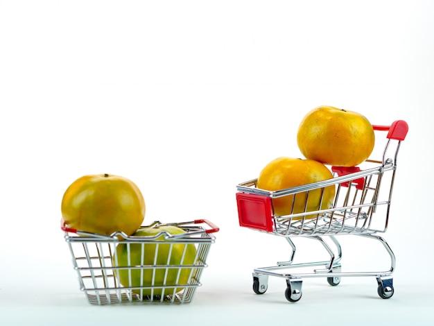 As laranjas frescas e carrinho de compras, conceito de compras de cesta com fundo branco Foto Premium