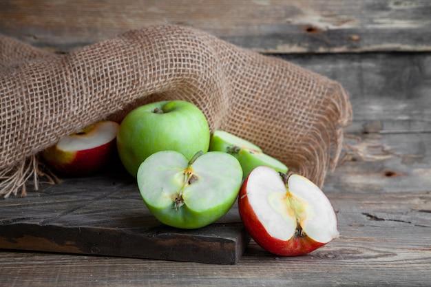 As maçãs verdes e vermelhas da vista lateral cortaram ao meio na madeira, no pano e no fundo de madeira escuro. horizontal Foto gratuita