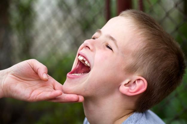 As mães entregam lovingly guardar o queixo do menino considerável de sorriso pequeno que mostra seus dentes engraçados brancos da criança ao ar livre. relações familiares felizes, cuidados de saúde e conceito de problemas dentários. Foto Premium