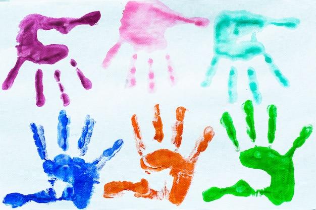 As mãos coloridas imprimem da aguarela. Foto Premium