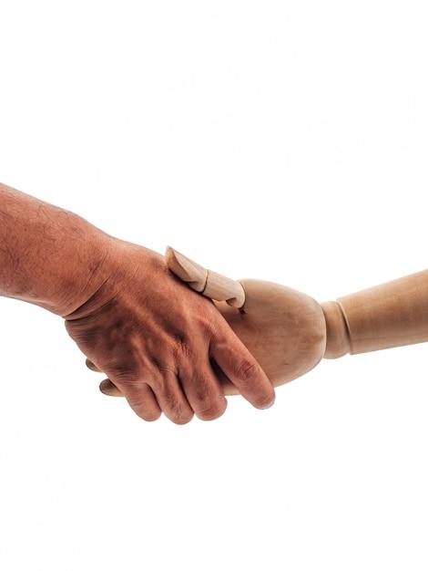 As mãos da boneca de madeira estão segurando a mão humana em branco Foto Premium