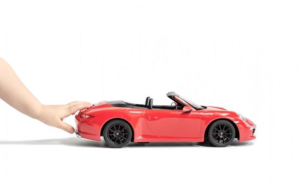 As mãos da criança empurrando o carro de brinquedo de coral porsche carrera s 911 modelo Foto Premium
