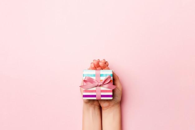 As mãos da fêmea segurando uma caixa de presente listrada com fita colorida na vida coral fundo. conceito de natal ou outra caixa de presente artesanal de férias, vista superior do conceito com espaço de cópia Foto Premium