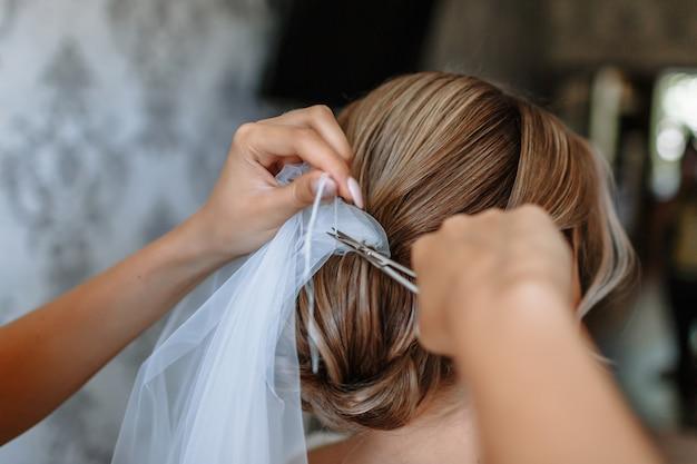 As mãos da menina cortam o fio que segura o véu do casamento Foto Premium