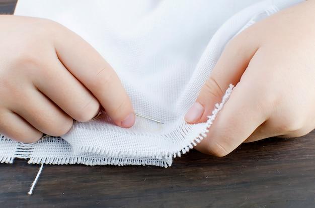 As mãos da menina que embroiding cruzam na lona. Foto Premium