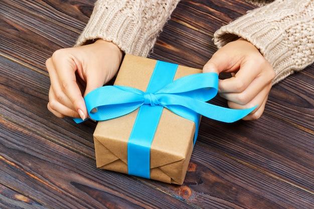 As mãos da mulher dão o valentim envolvido ou o outro presente feito a mão do feriado no papel com fita azul. Foto Premium