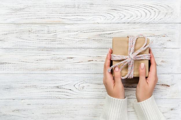 As mãos da mulher dão o valentim envolvido ou o outro presente feito a mão do feriado no papel com fita cor-de-rosa. Foto Premium