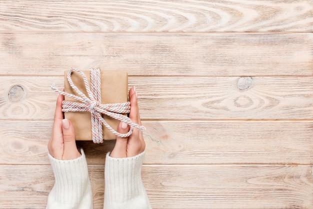 As mãos da mulher dão valentim envolvido no papel com fita vermelha. Foto Premium