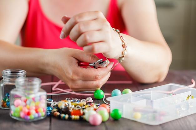 As mãos da mulher fazendo bracelete com contas de plástico Foto Premium