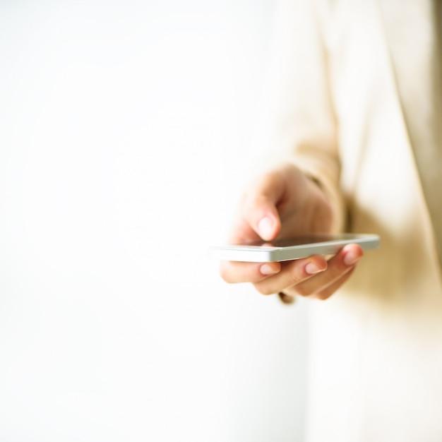 As mãos da mulher guardam o telefone celular no fundo do creme claro. negócios, estudo, trabalho remoto, sempre conecte o conceito. smartphone. Foto Premium