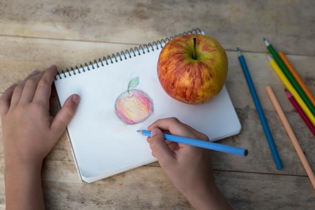 As mãos das crianças desenham uma maçã com lápis de cor. vista do topo Foto Premium