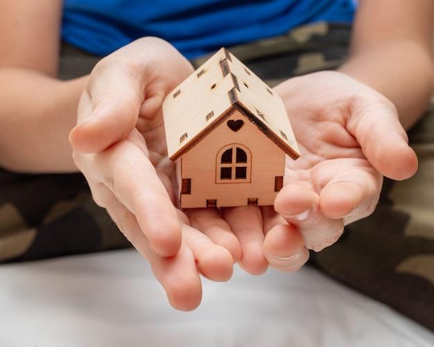 As mãos das crianças seguram uma pequena casa de madeira. um símbolo de família, conforto do lar, doce lar. Foto Premium