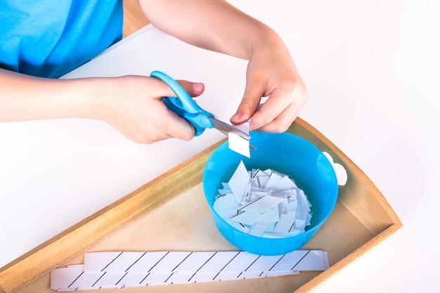As mãos das crianças seguram uma tesoura azul e cortam o papel. Foto Premium